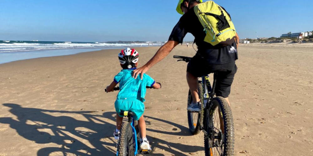 Foto de padre ayudando a hija en bici con un Objetivo 2021: subir a la bici a alguien querido en 30 Días en bici
